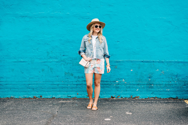 summer outfit colorful, jean jacket, white tee shirt, printed shorts, wide brim straw sun hat, leather slides sandals, pale pink crossbody bag