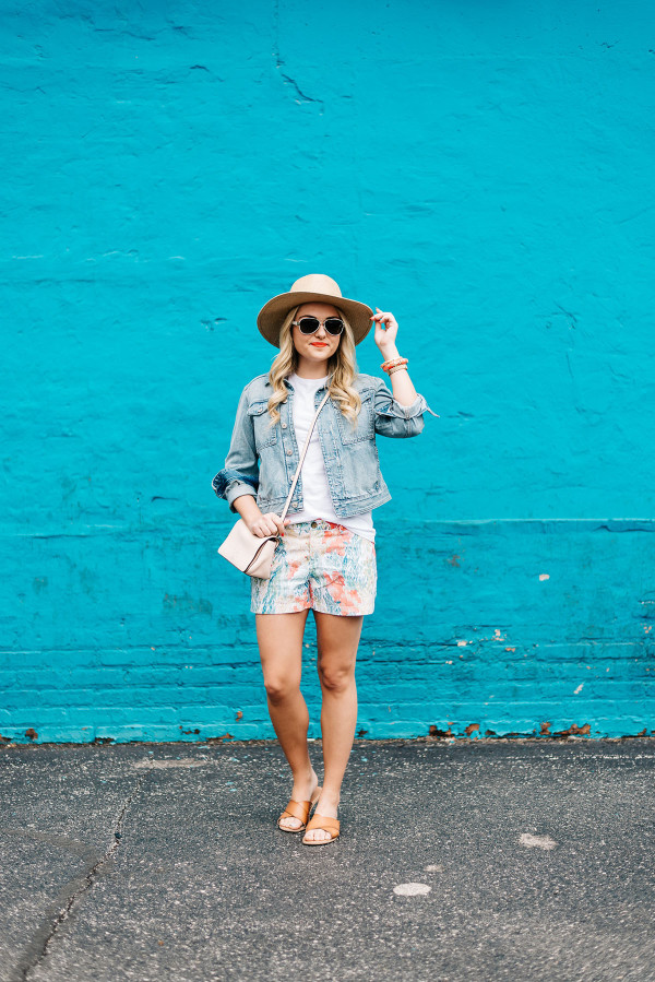 summer outfit ideas straw hat, denim jacket, printed shorts, leather sandals, blush pink crossbody bag, summer concert outfit
