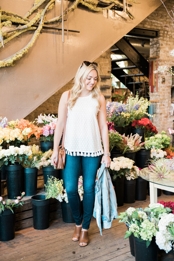 Fashion blogger, Jessica Sturdy, inside of A New Leaf flower shop on Wells Street in Lincoln Park in Chicago. She's wearing an Old Navy tassel top, J Brand jeans, J.Crew leather mules, and an Express denim jacket.