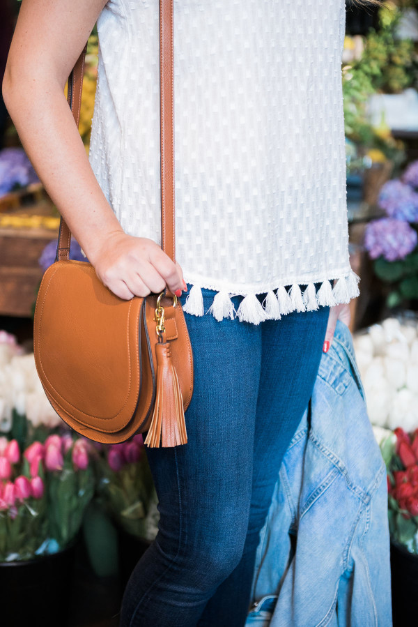 Fashion blogger, Jessica Sturdy, inside of A New Leaf flower shop on Wells Street in Lincoln Park in Chicago. She's wearing an Old Navy tassel top, J Brand jeans, a brown leather crossbody bag with a tassel, and an Express denim jacket.
