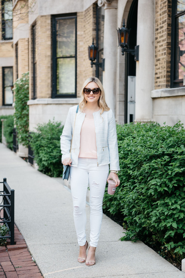 Fashion blogger, Jessica Sturdy of Bows & Sequins, wearing a light blue tweed jacket, a coral tee, white ripped jeans, and nude ankle-strap sandals.