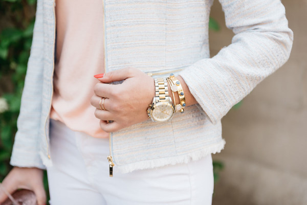 Bows & Sequins wearing a coral-colored tee shirt and a metallic, light-blue tweed jacket.