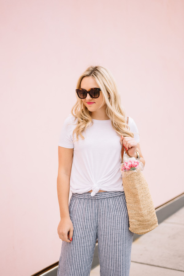weekend outfit white tee shirt, straw tote, blue and white striped linen pants
