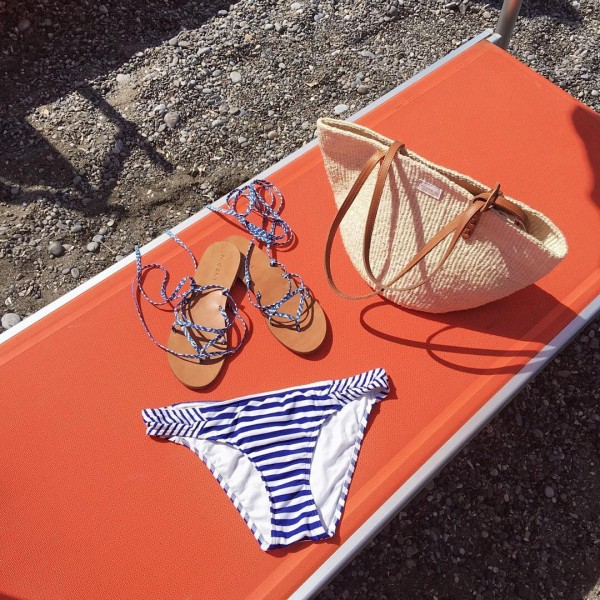 Bows & Sequins at a beach club in Positano! Blue and white striped bikini from Wala Swim, M.Gemi lace-up sandals, and a Clare V straw tote.