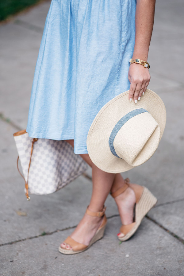 Bows & Sequins wearing a Banana Republic ruffled v-neck dress, Club Monaco straw hat, Louis Vuitton Damier Azur Neverfull Tote, Express cat-eye sunglasses, and Vince Camuto leather espadrille wedges to the Veuve Clicquot Polo Classic in New York.