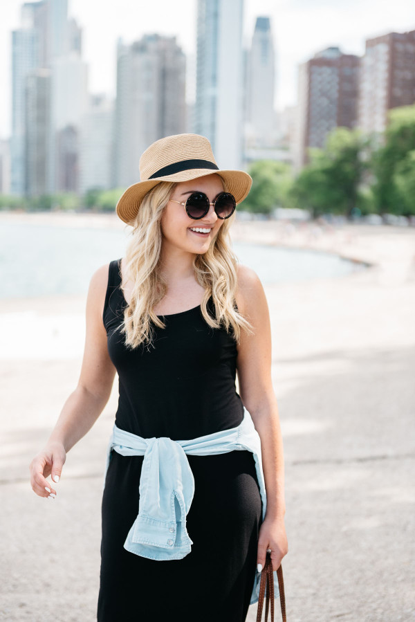 Bows & Sequins at North Avenue Beach in Chicago wearing a black maxi dress and chambray shirt with a straw hat and round glitter sunglasses.