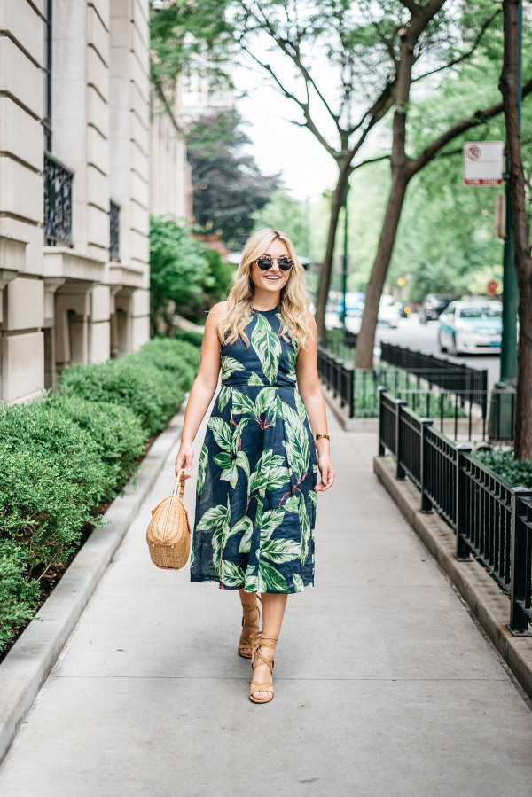 Blogger Jessica Sturdy (@bowsandsequins) wearing an Ann Taylor leaf print halter dress, Illesteva tortoise sunglasses, a J.McLaughlin wicker rattan handbag, and Ivanka Trump lace-up sandals in the Gold Coast in Chicago.