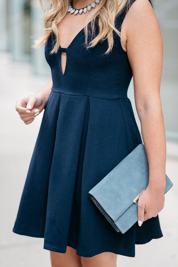 Bows & Sequins styling a navy fit & flare dress, Loren Hope necklace, Ivanka Trump blue suede clutch, and Vince Camuto lace-up sandals.