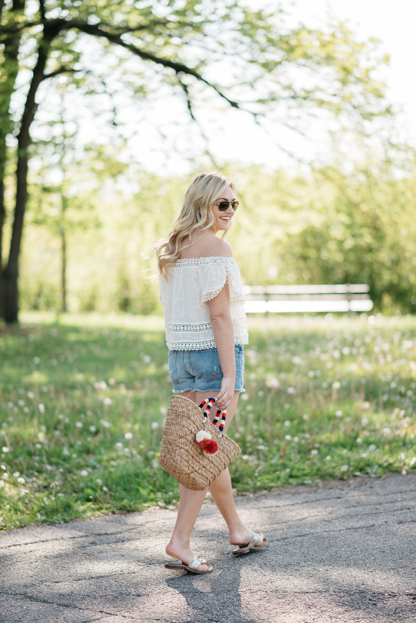 Bows & Sequins styles a pair of cut off shorts with a gauzy off-the-shoulder top, Jack Rogers sandals, and a Kayu pom pom tote.
