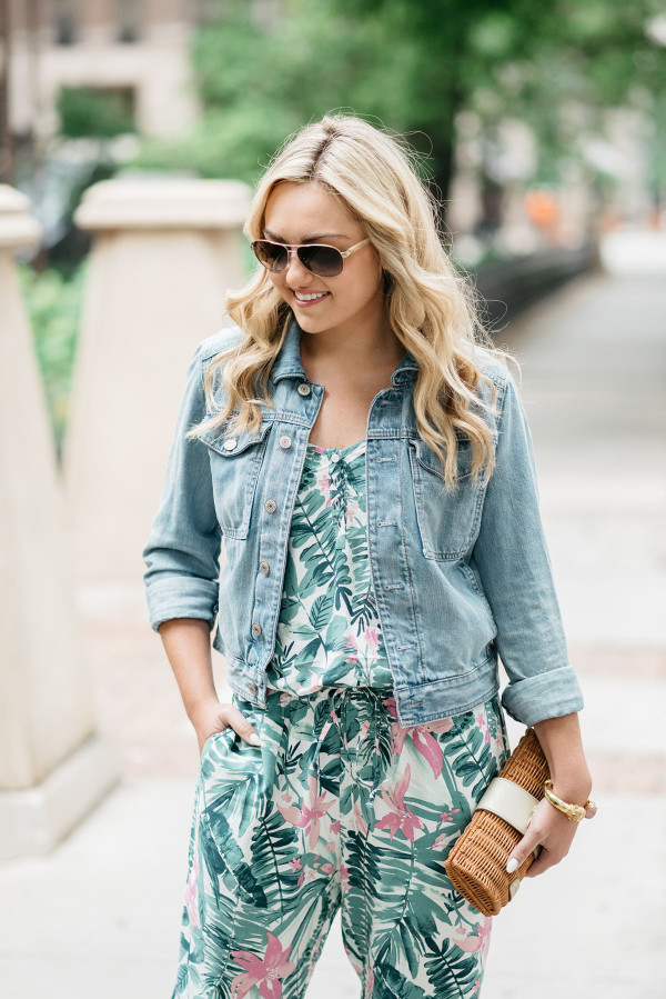 Bows & Sequins tackling the tricky trend of wearing a printed jumpsuit. She paired the leaf-printed, tropical jumpsuit with a denim jacket, lace-up heels, aviator sunglasses, and a rattan clutch.
