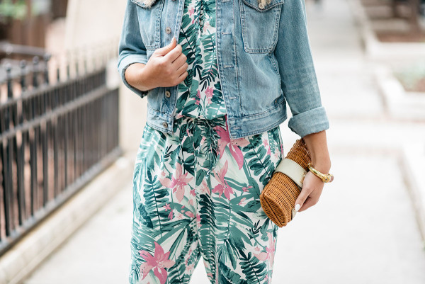 Bows & Sequins tackling the tricky trend of wearing a printed jumpsuit. She paired the pink and green leaf-printed, tropical jumpsuit with a denim jacket and a rattan clutch.