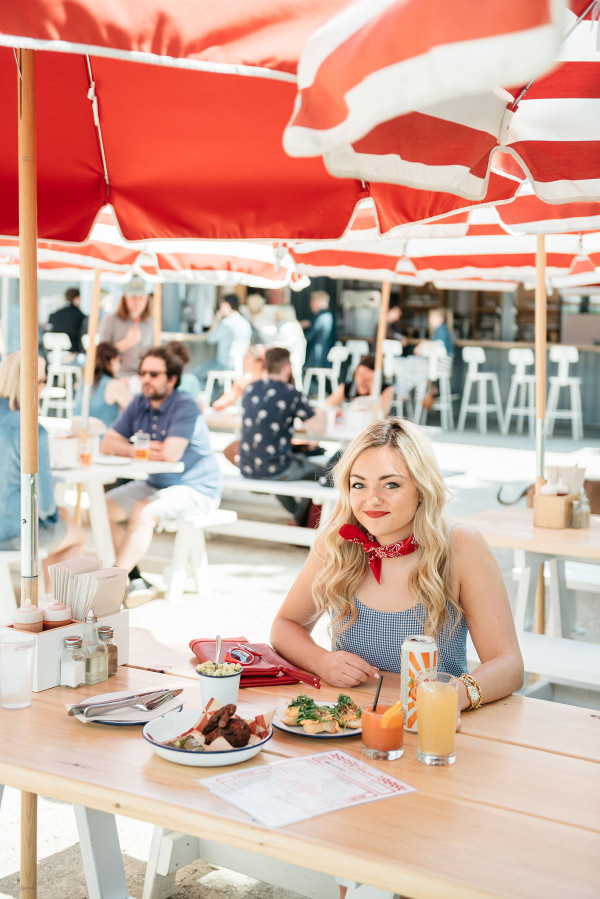 Bows & Sequins visits Parson's Chicken and Fish in Chicago. Jessica is wearing a white and blue gingham top with all red accessories: a red bandana tied around her neck, a red clutch, red sunglasses, and red lipstick. A fun Americana-inspired outfit that's perfect for Fourth of July festivities!