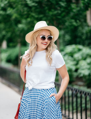 Bows & Sequins wearing an Americana Red, White, and Blue outfit for July 4th weekend! A white Old Navy knotted tee, a blue and white J.Crew gingham skirt, a Club Monaco straw hat, a red Ralph Lauren handbag, and Vince Camuto leather espadrille wedges.