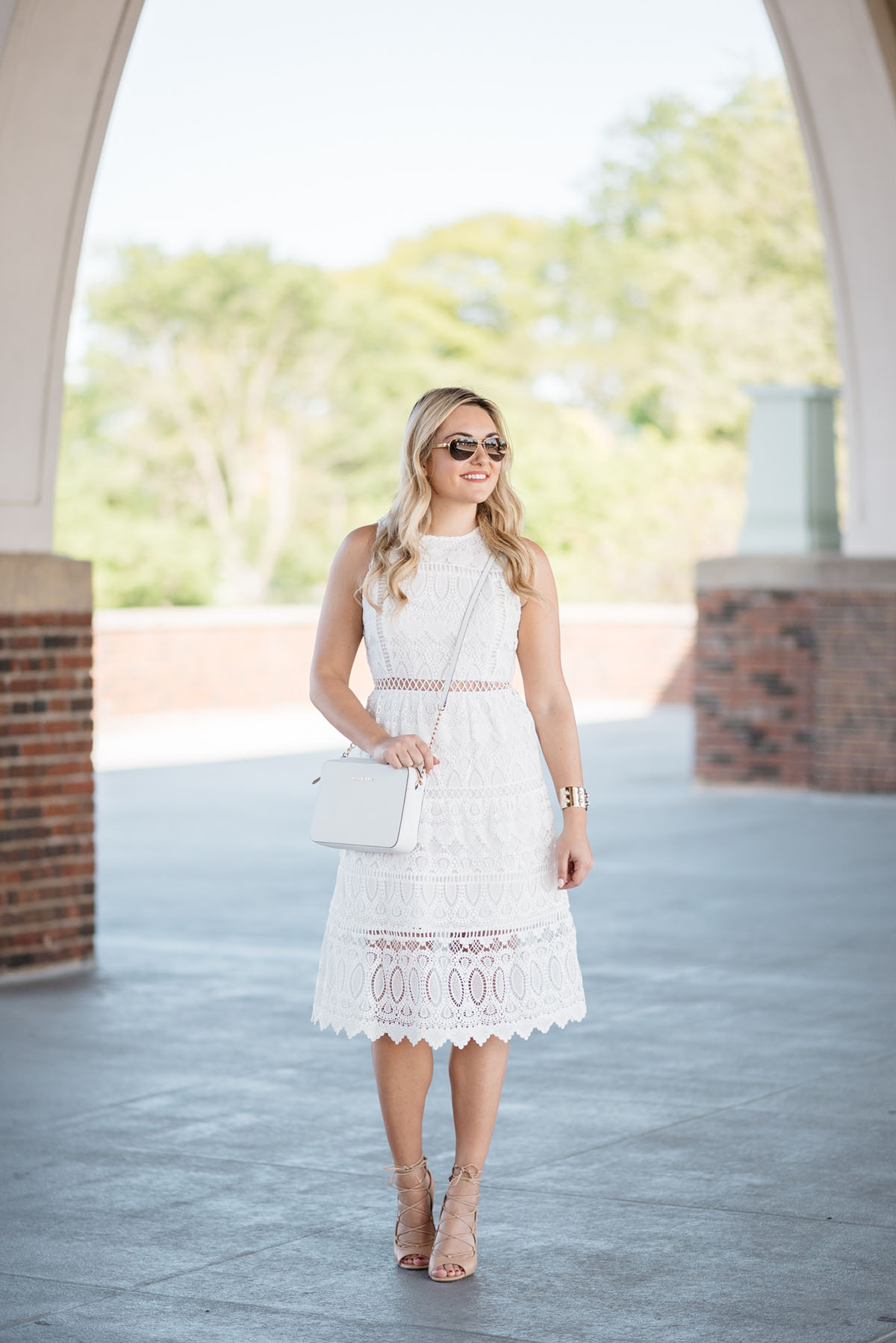 Bows & Sequins wearing a white lace dress, white crossbody bag, and tan lace-up heels in Chicago.