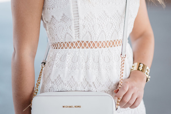 Bows & Sequins wearing a white lace dress and a Michael Kors white crossbody bag in Chicago.