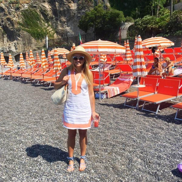 Bows & Sequins at a Positano Beach Club on the Amalfi Coast with orange and white striped umbrellas. Wearing an orange and white linen tunic from Sail to Sable!