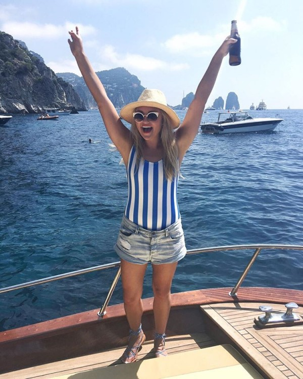 Bows & Sequins on the Amalfi Coast on a boat tour of Capri wearing a blue and white striped one-piece swimsuit!