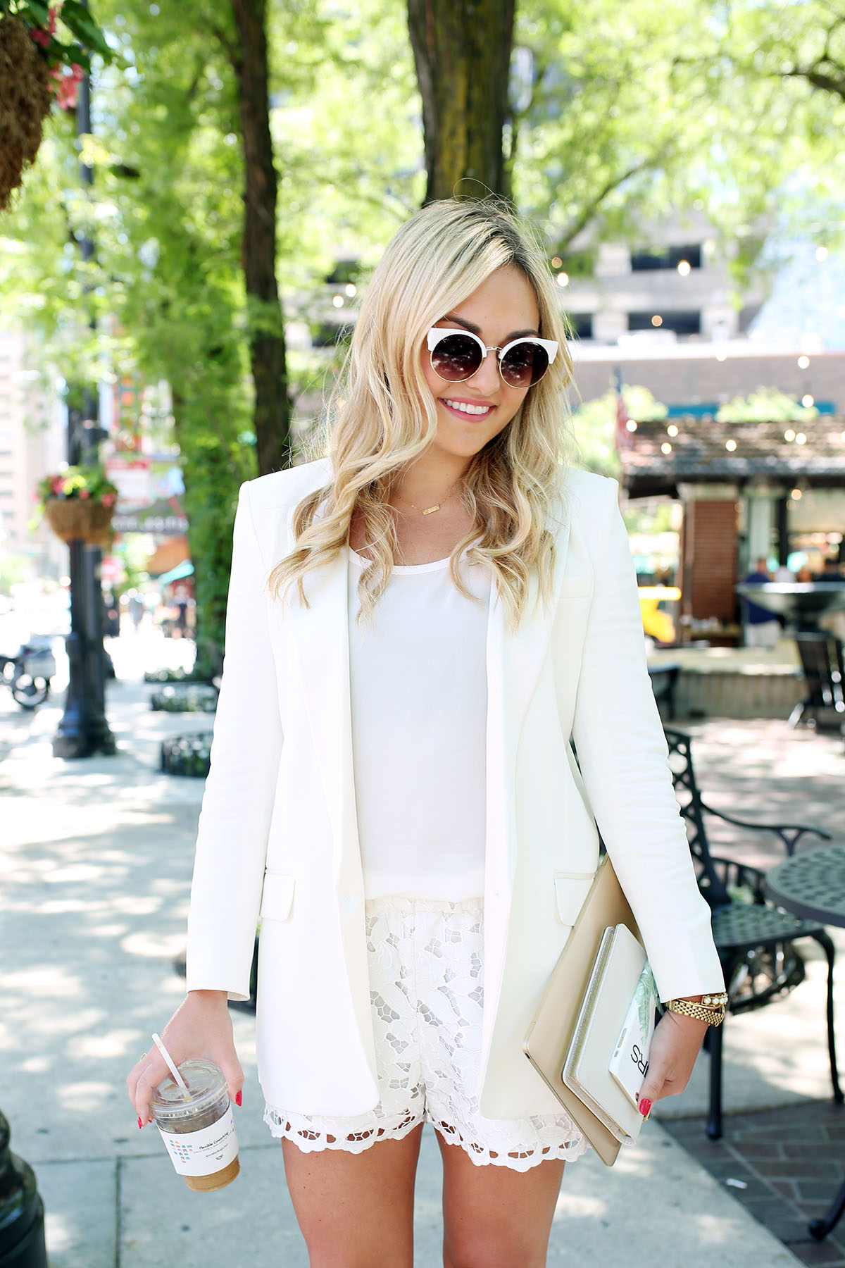 Bows & Sequins wearing an all-white outfit that's perfect for going from the workday to dinner and drinks! Pair a long-line white blazer with a silky tank and lace shorts for a chic summertime look.