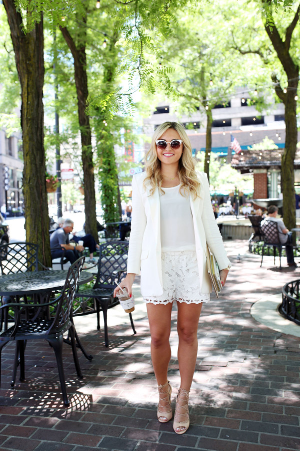 Bows & Sequins wearing an all-white outfit that's perfect for going from the workday to dinner and drinks! Pair a long-line white blazer with a silky tank, lace shorts, and lace-up heels for a chic summertime look.