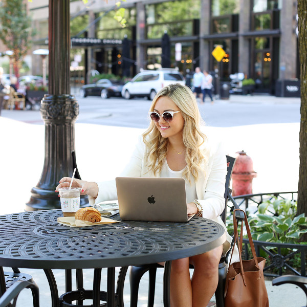Bows & Sequins working on her computer at the outdoor Bow Truss coffee shop in the Gold Coast at Mariano Park in Chicago. She's wearing an all-white summertime outfit made up of a long-line blazer, a silky tank top, lace shorts, and lace-up leather heels.