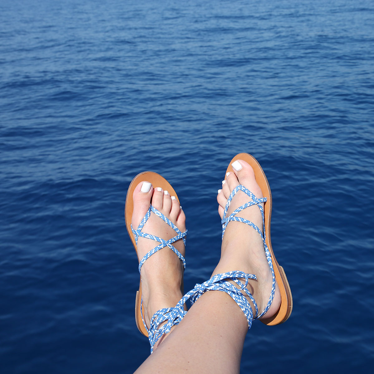 Bows & Sequins sailing on the Mediterranean Sea from Positano to Capri on the Amalfi Coast. Wearing a pair of lace-up M.Gemi sandals!