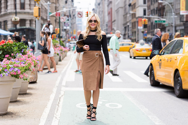 Bows & Sequins wearing a black off-the-shoulder crop top, a black choker, a suede wrap skirt with a thigh slit, and lace-up black heels in New York City by the iconic Flatiron Building near Madison Square Park.