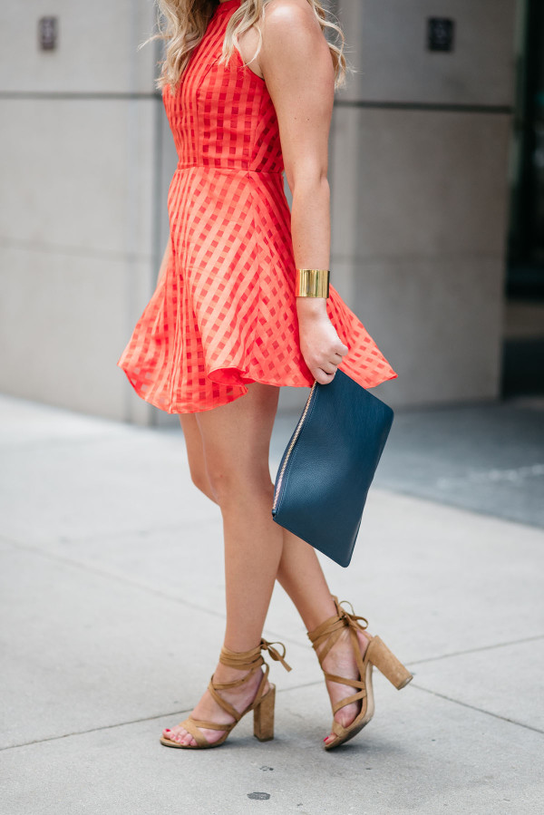 Bows & Sequins wearing a Lovers + Friends red-orange dress with a gold cuff, a navy blue leather clutch, and nude lace-up suede sandals.