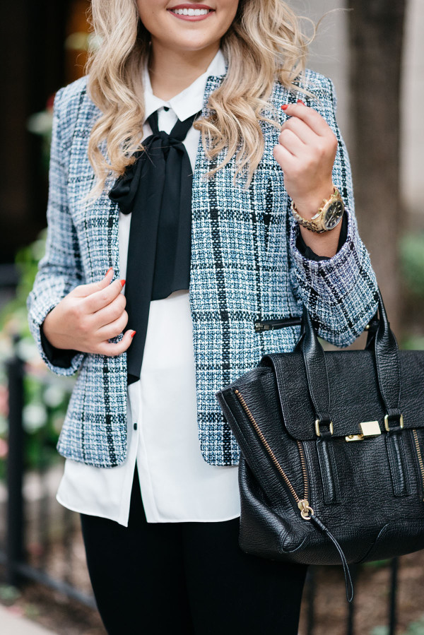 Bows & Sequins wearing a tweed jacket, a bow-tied blouse, black jeans, and a 3.1 Phillip Lim Pashli bag.
