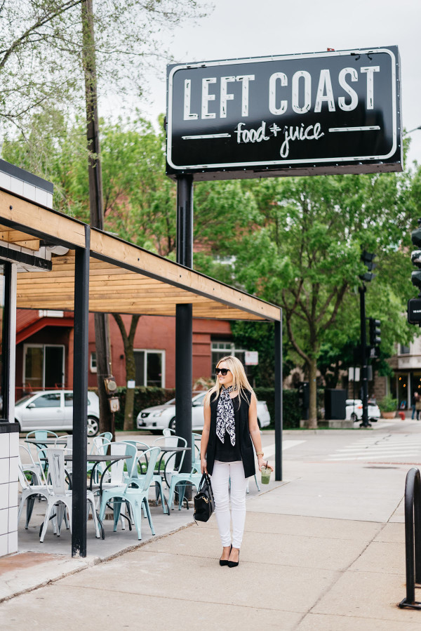 Bows & Sequins styles a casual summertime work outfit: white denim jeans, a silky blank tank top, a long black vest, a scarf tied at the neck, black pointed toe pumps, and a black tote!