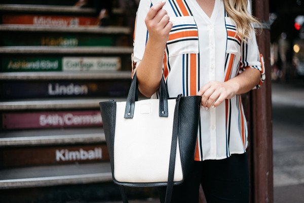 Chicago Blogger Jessica Sturdy of Bows & Sequins styling a striped button-front shirt, black skinny jeans, and a color-blocked black and white tote for a work-appropriate outfit in front of the Chicago El Train steps in the Loop downtown.