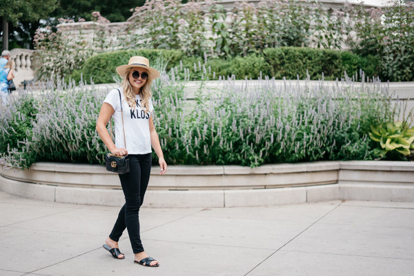 Chicago Blogger Jessica Sturdy of Bows & Sequins styling an Express t-shirt and black skinny jeans with black criss-cross leather slides, a Janessa Leone straw hat, a black and gold Gucci bag, and big round sunglasses in Millennium Park.