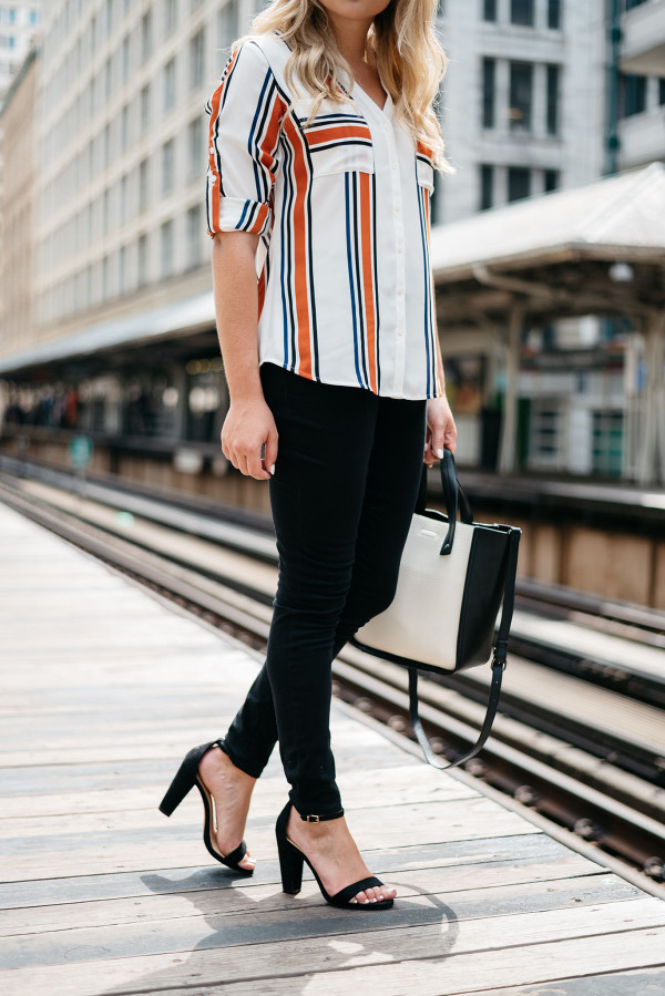 Chicago Blogger Jessica Sturdy of Bows & Sequins styling a striped button-front shirt, black skinny jeans, ankle-strap heels, and a color-blocked black and white tote for a work-appropriate outfit on the Chicago El Train platform in the Loop downtown.