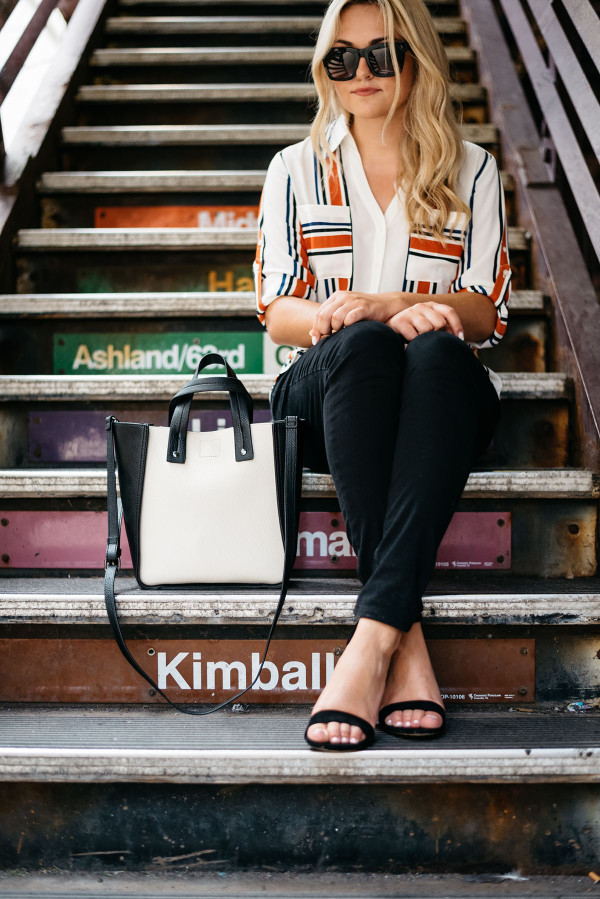 Chicago Blogger Jessica Sturdy of Bows & Sequins styling a striped button-front shirt, black skinny jeans, ankle-strap heels, and a color-blocked black and white tote for a work-appropriate outfit in front of the Chicago El Train steps in the Loop downtown.