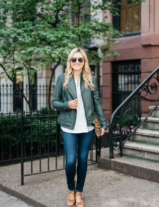 Bows & Sequins wearing a green leather jacket with jeans and a leopard clutch for fall.