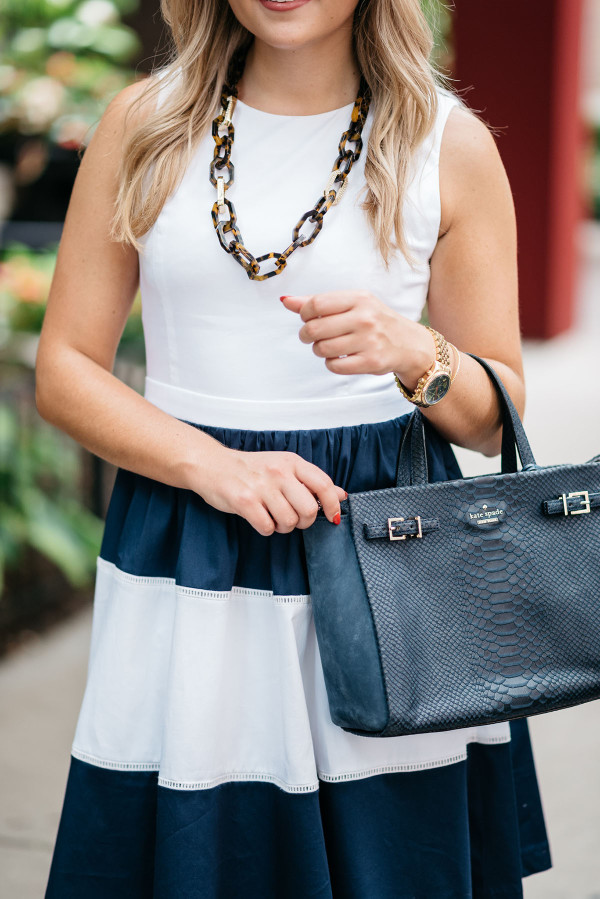 Blogger @bowsandsequins wearing a navy and white striped Elizabeth McKay dress with a gold watch with a navy face, a navy blue Kate Spade bag, and a tortoise link necklace.