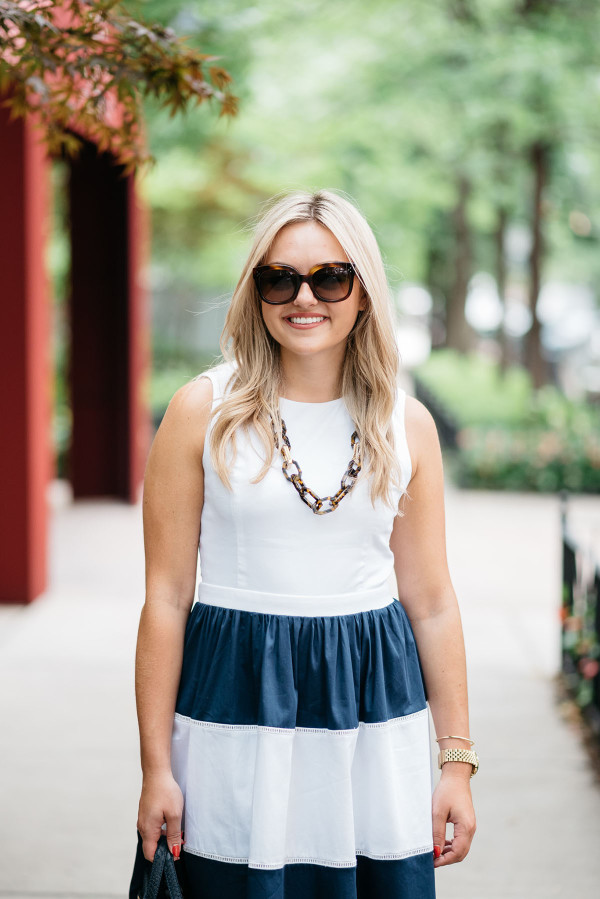 Blogger @bowsandsequins wearing a navy and white striped Elizabeth McKay dress with Celine sunglasses, a navy blue Kate Spade bag, and a tortoise link necklace.