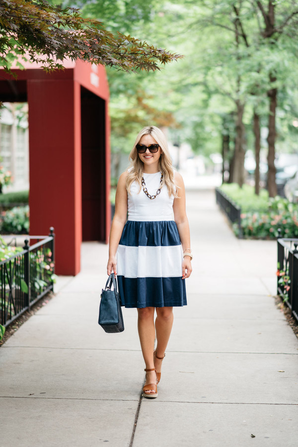 Blogger @bowsandsequins wearing a navy and white striped Elizabeth McKay dress with leather espadrille wedges, Celine sunglasses, a navy blue Kate Spade bag, and a tortoise link necklace.