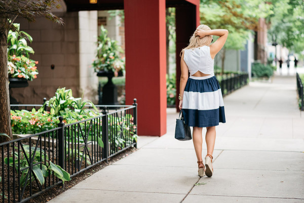Chicago fashion blogger Jessica Sturdy of @bowsandsequins wearing a navy blue and white striped dress with a cutaway back detail. She paired it with a navy handbag and leather espadrille wedges.