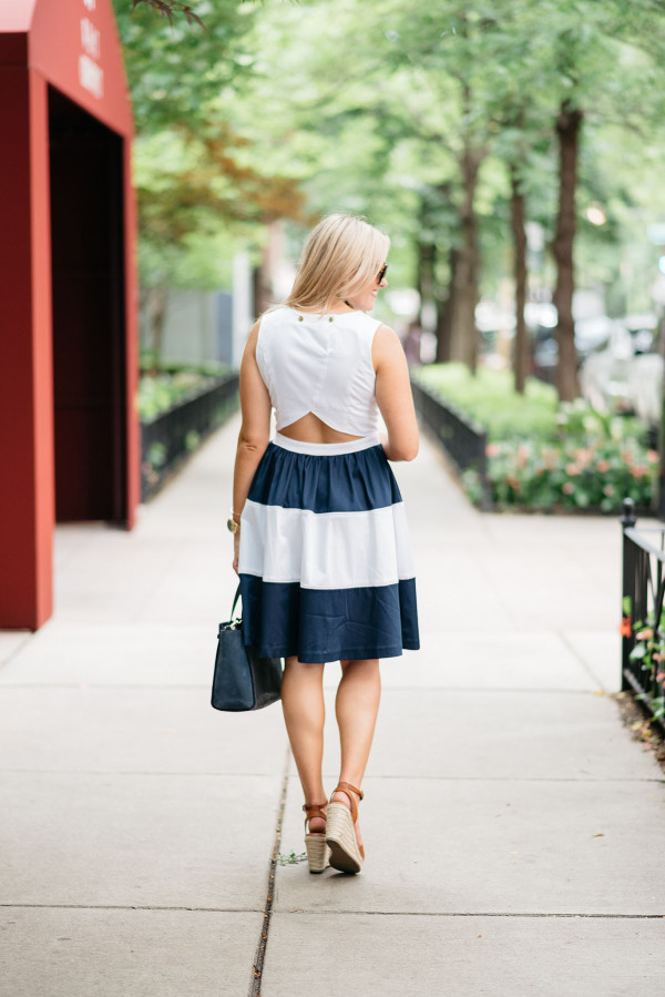 Blogger @bowsandsequins wearing a navy and white striped Elizabeth McKay dress with a cutout back styled with leather espadrille wedges, Celine sunglasses, a navy blue Kate Spade bag, and a tortoise link necklace.