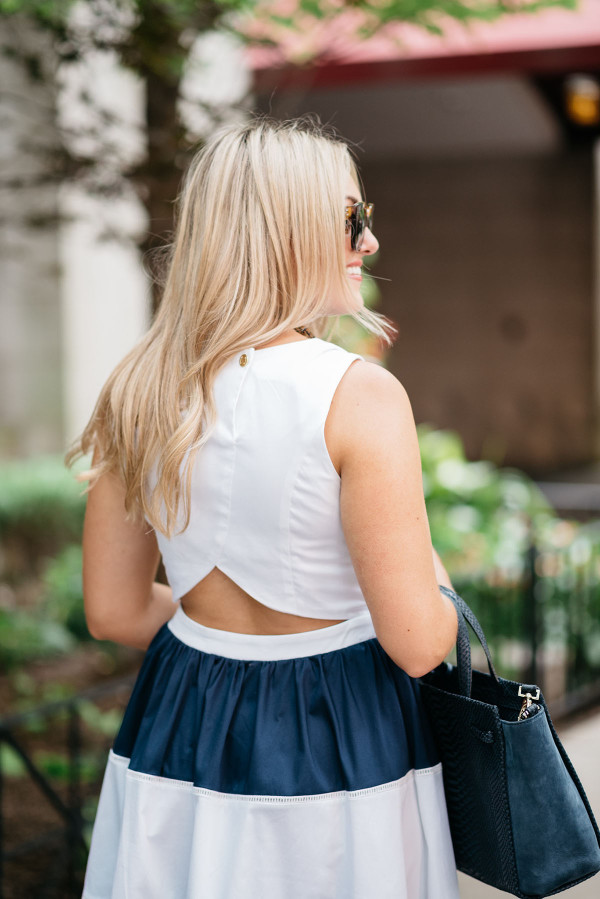 Blogger @bowsandsequins wearing a navy and white striped Elizabeth McKay dress with a cutout back styled with Celine sunglasses, a navy blue Kate Spade bag, and a tortoise link necklace.