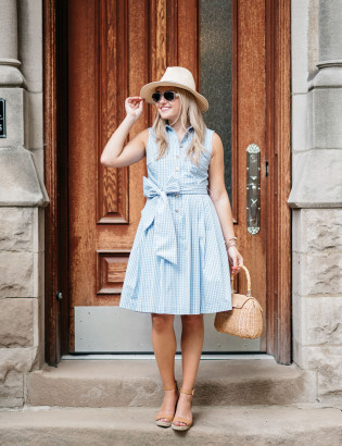 Blogger Jessica Sturdy of Bows & Sequins wearing a blue and white gingham dress with a big bow tie. Styled with a straw hat, wicker rattan tote, and espadrille wedges for a summertime Saturday outfit!