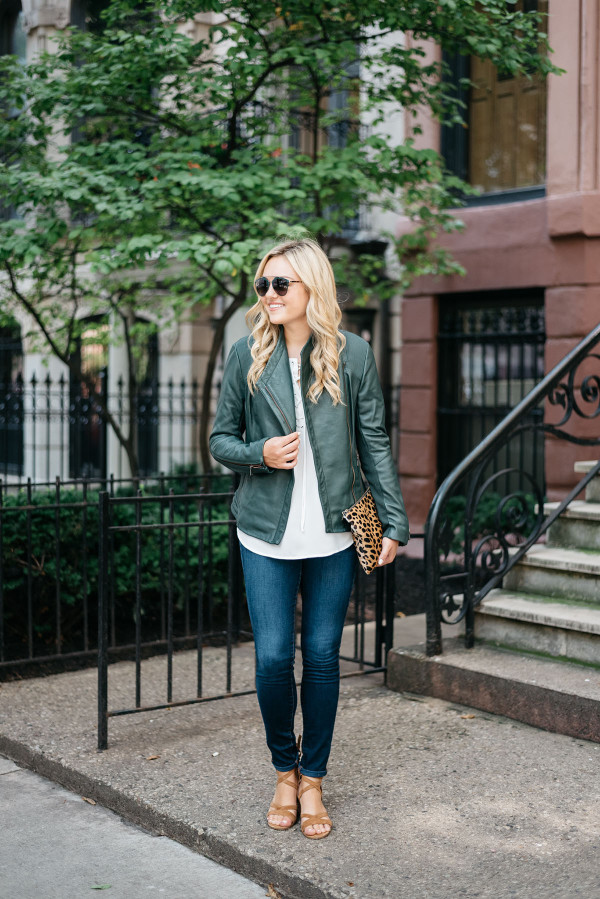Bows & Sequins wearing a green leather jacket, a white lace-up blouse, jeans, a leopard clutch, and lace-up sandals.