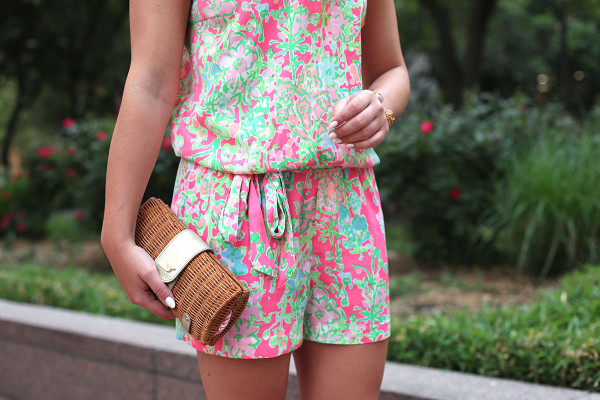 Bows & Sequins wearing a printed Lilly Pulitzer romper with a wicker clutch.