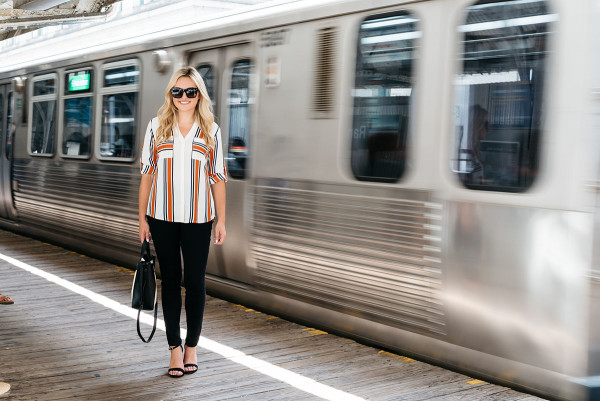 Chicago Blogger Jessica Sturdy of Bows & Sequins styling a striped button-front shirt, black skinny jeans, ankle-strap heels, and a color-blocked black and white tote for a work-appropriate outfit on the Chicago El Train platform in the Loop downtown. Moving subway car photo captured by Iron & Honey.