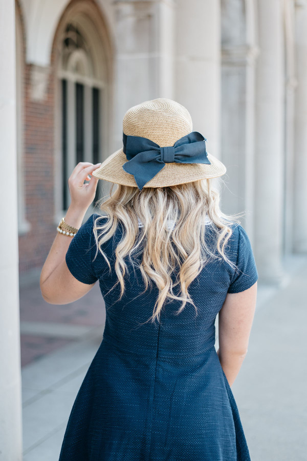 Bows & Sequins styling a navy fit and flare dress with a straw hat with a navy grosgrain bow!