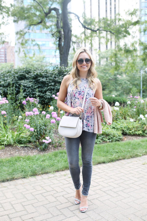 Fashion blogger Bows & Sequins wearing grey jeans, a floral paisley-printed top from Old Navy, a Kate Spade crossbody bag, and Dior sunglasses.
