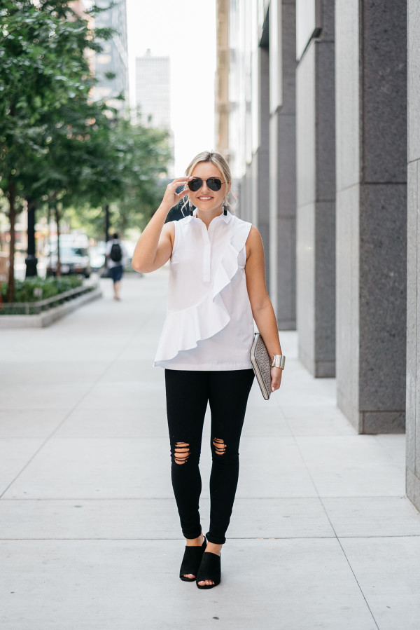 Bows & Sequins styling a white ruffled sleeveless collared shirt, black destroyed denim, black suede mules, and black Ray-Ban aviator sunglasses.
