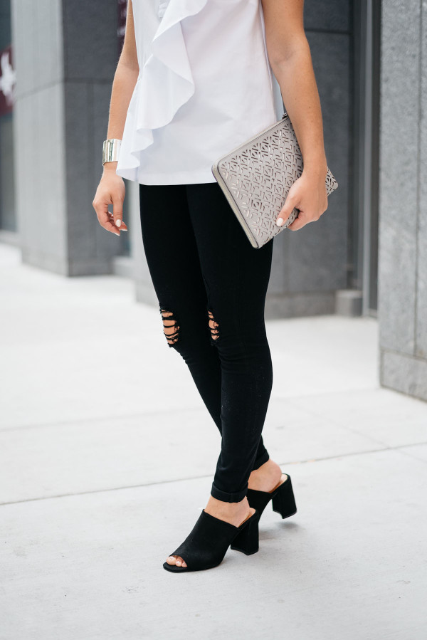Bows & Sequins wearing a white ruffled top, black destroyed denim, and black suede mules.