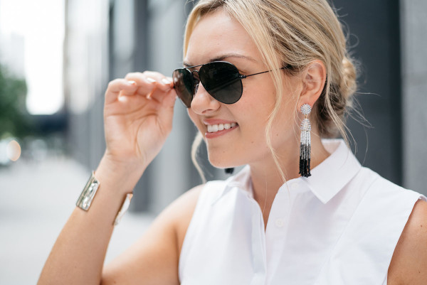 Bows & Sequins styling a white ruffled sleeveless collared shirt, tassel drop earrings, and black Ray-Ban aviator sunglasses.