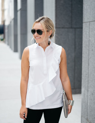 Bows & Sequins styling a white ruffled sleeveless collared shirt, black destroyed denim, tassel drop earrings, a metallic cut-out clutch, and black Ray-Ban aviator sunglasses.